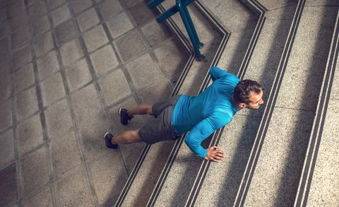 Above view of sportsman exercising push-ups on the stairs.
