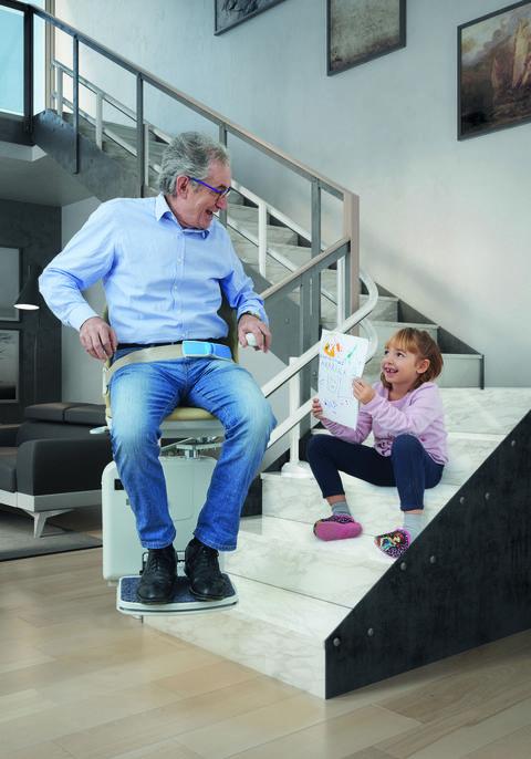 abuelo, con un salvaescaleras de válida sin barreras, y nieta charlan en una escalera
