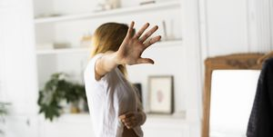 Abuse and violence against women, woman raising hand at home