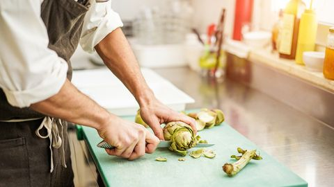Midsection Of Man Cutting Artichoke In Kitchen