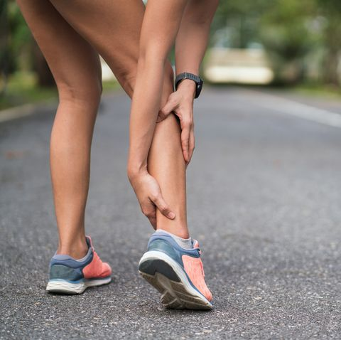Achilles injury on running outdoors. Women holding Achilles tendon by hands close-up and suffering with pain. Ankle twist sprain accident in sport exercise running jogging.