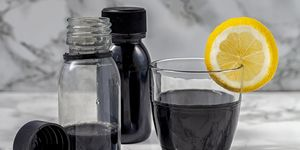 Activated charcoal detox juice drink or black lemonade whit coconut, green apple and lime on white marble background