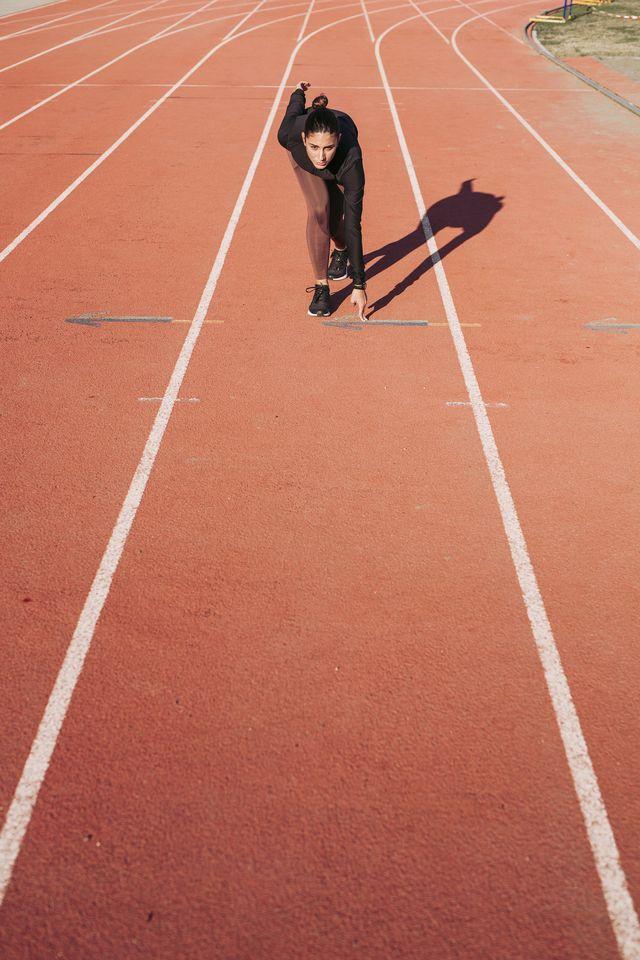 jonge vrouw op tartan atletiekbaan maakt zich klaar om te hardlopen