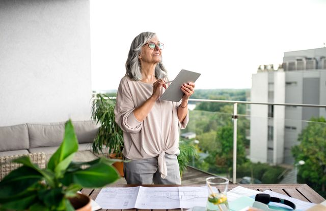 active senior architect with tablet in home office, working outdoors on balcony
