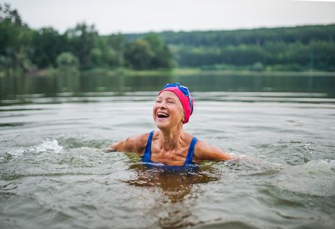 mujer mayor en medio de un lago, sonriendo