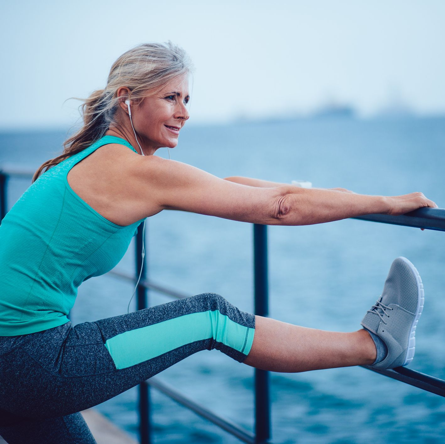 Active senior woman warming up by the sea for jogging