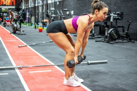 active sportive athletic woman doing deadlift exercise with dumbbell in gym