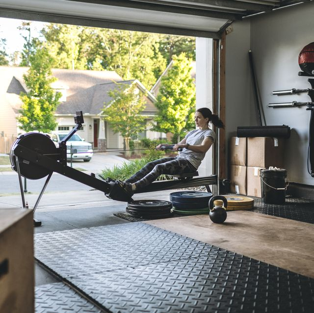 home gym equipment active woman exercising on a rowing machine in her home garage gym during covid 19 pandemic