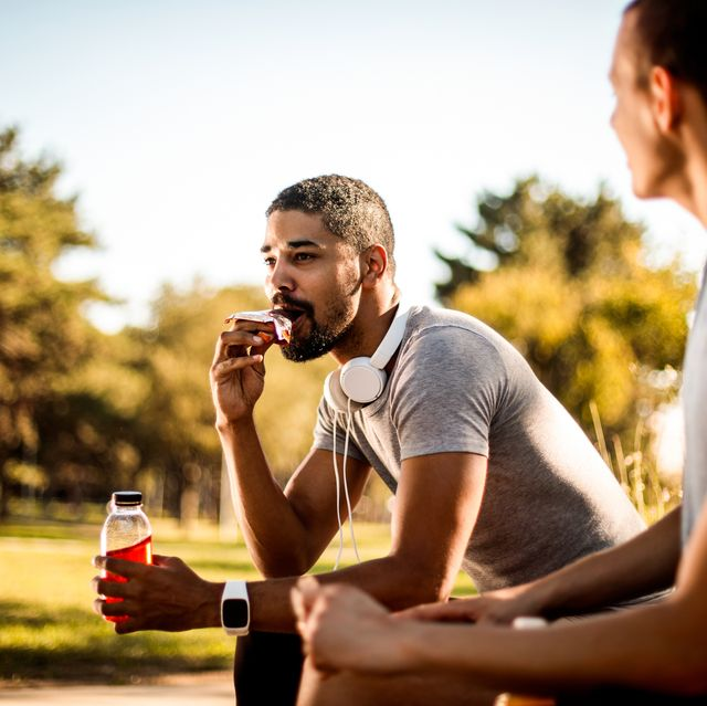 active young male taking a bite out of an protein bar and hydrating himself with a sport drink next to his friend