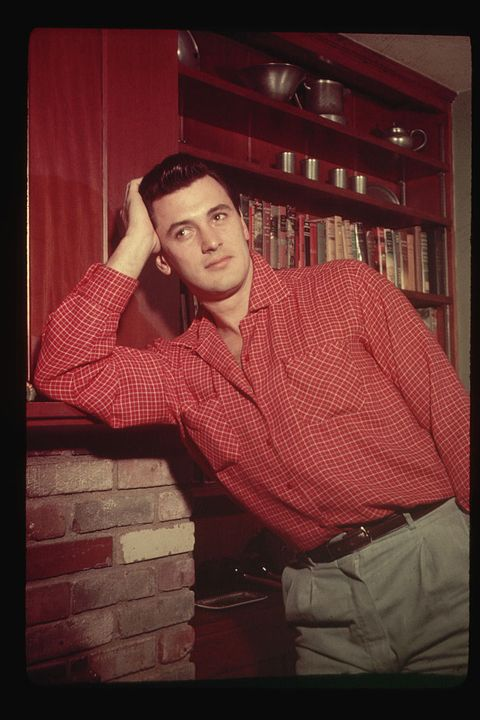 rock hudson leaning on a fireplace mantle