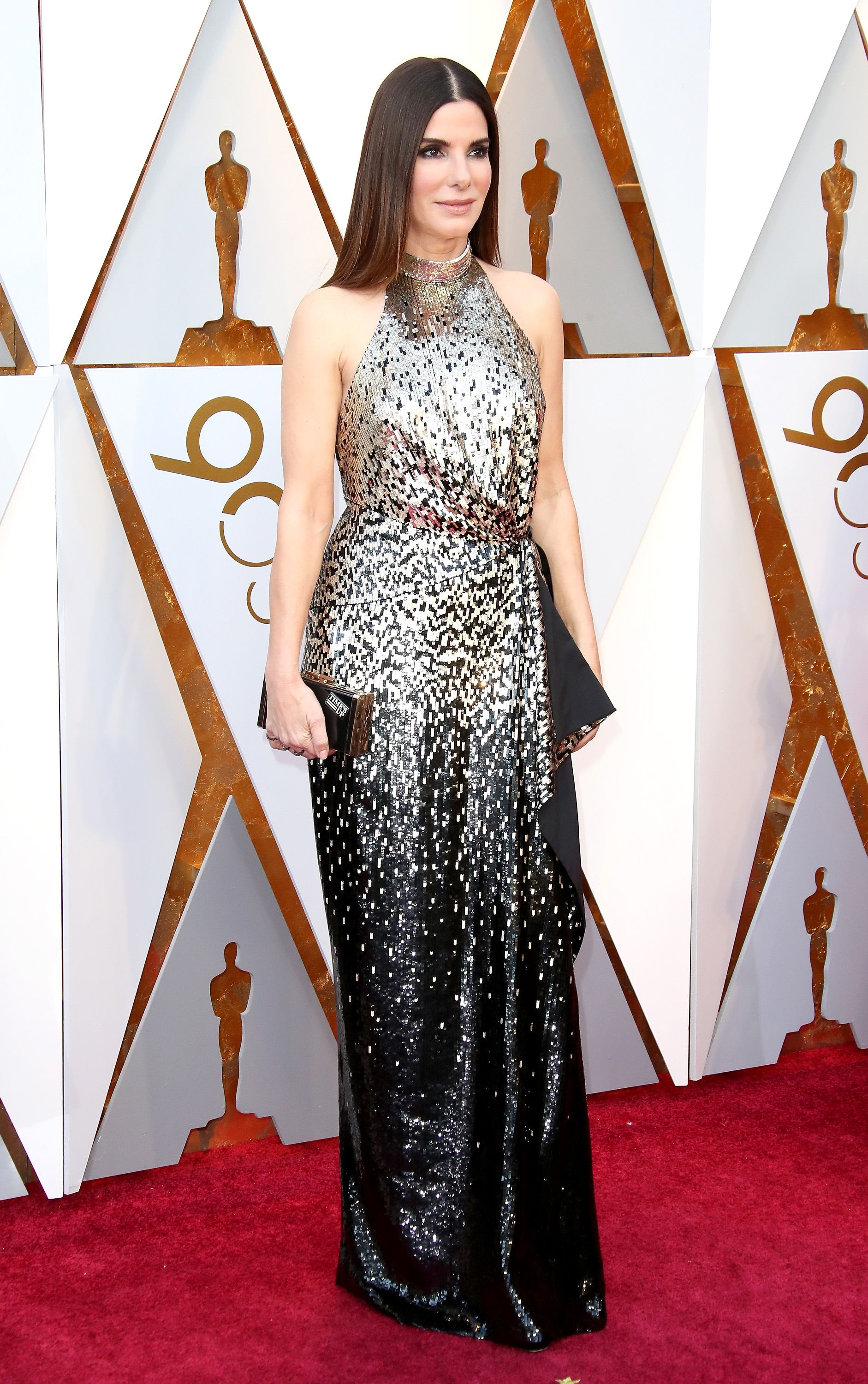Bullock donned a high-neck, silk Louis Vuitton halter gown with gold and black sequins at the 2018 Oscar Awards.