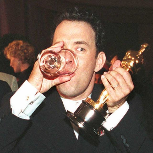 US actor Tom Hanks holds up his Oscar as he drinks