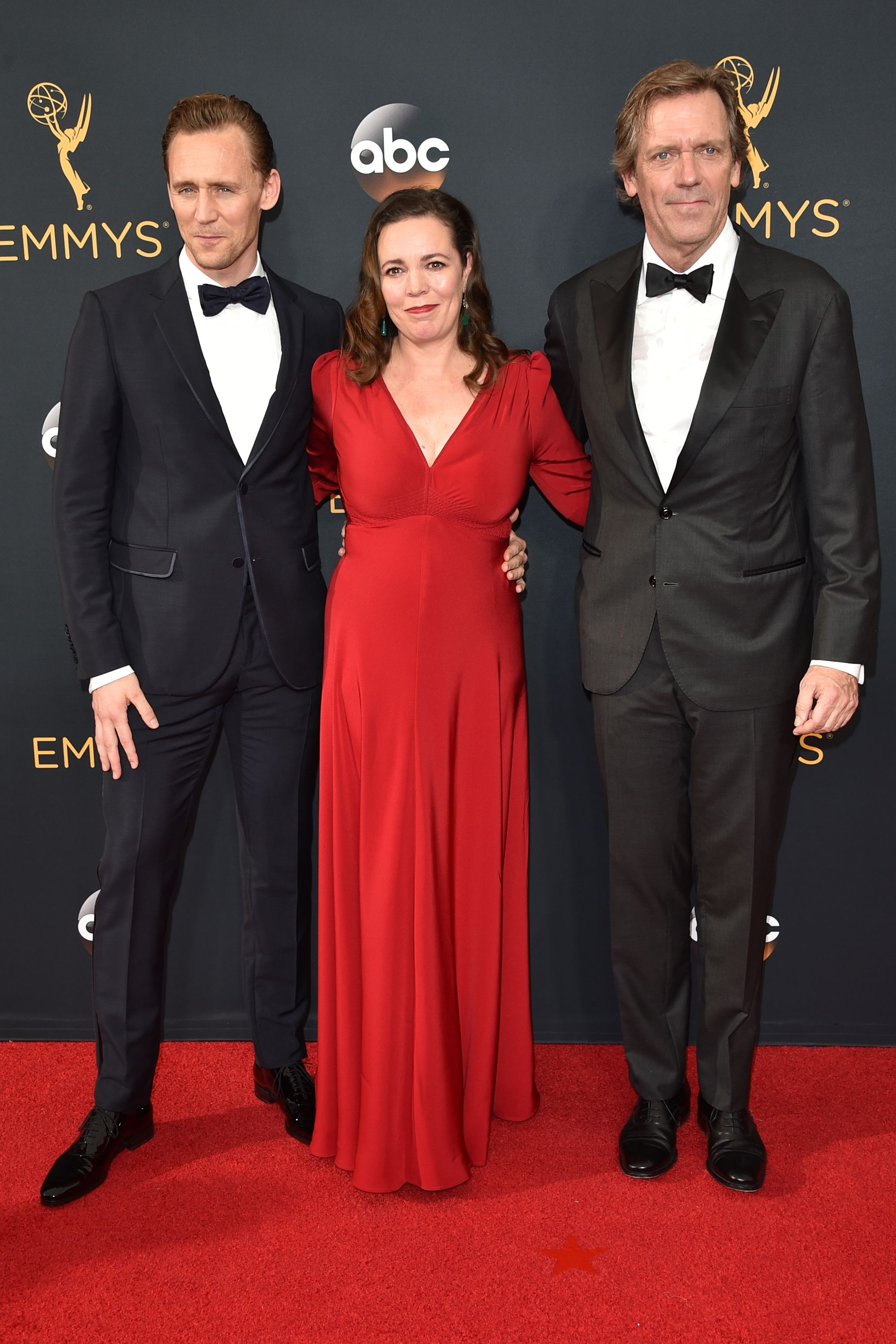 The actress chose a deep-red gown paired with diamond and emerald drop earrings for the Emmys, in which she was nominated for her role in The Night Manager .