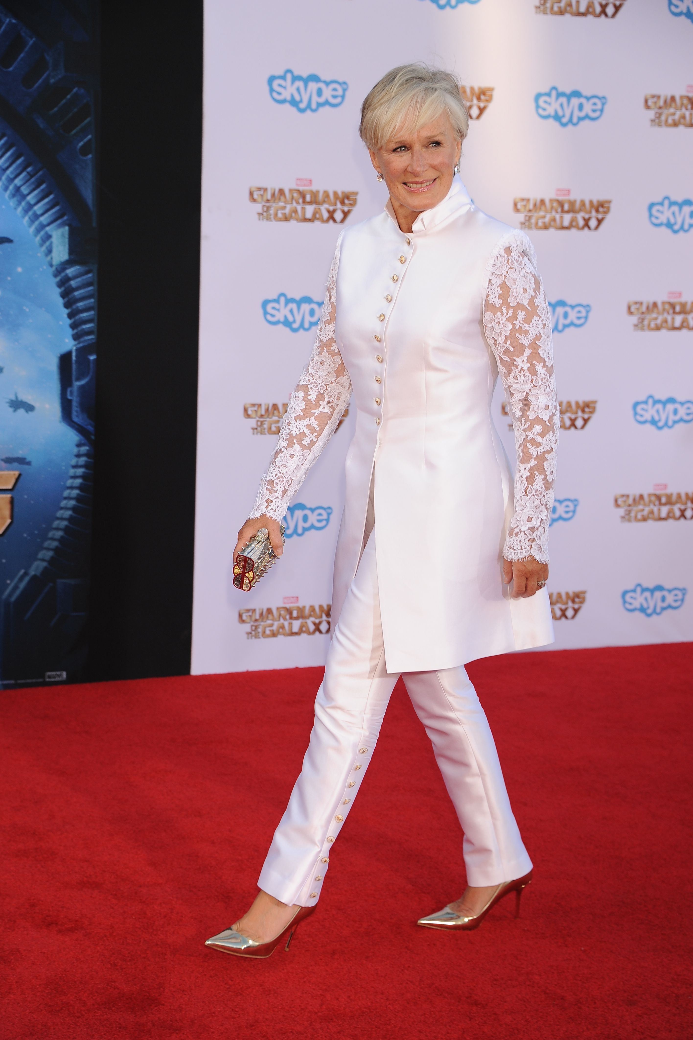 Glenn Close looked stunning at the Guardians of the Galaxy premiere in a white silk trouser suit with lace sleeves and gold button detailing. She paired the look with a gold clutch, earrings, and gold patent pumps.