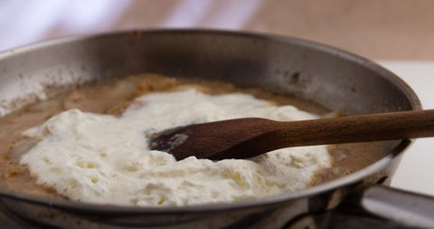 Adding whipped double cream to prepare onion sauce.