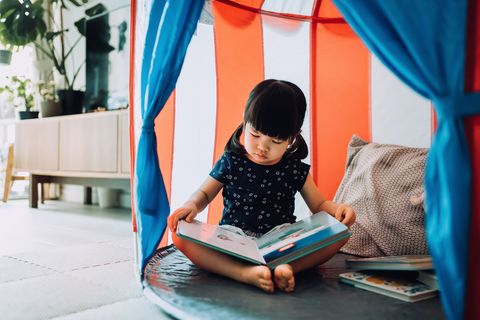 adorable little asian girl enjoying herself and spending leisure time at home she is reading book with her teddy bear in a tent at home