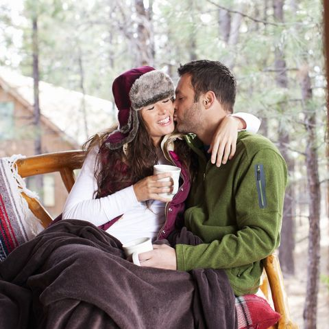 Adorable Young Couple Kissing Outdoors at Winter Cabin