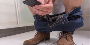 Adult male wearing jeans and shoes using phone while sitting