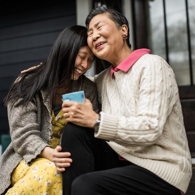 adult woman and senior mother talking on front porch