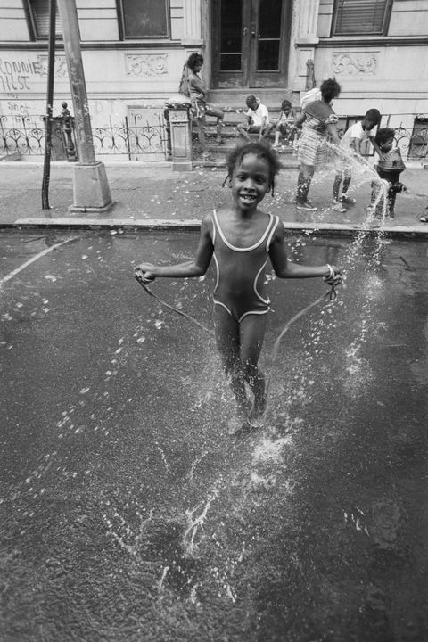 little girl skips in spray of hydrant