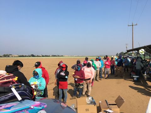 farm workers wait in line for donated school supplies