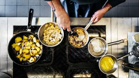 Aerial Shot Of Chef Cooking On The Hob In Restaurant Kitchen
