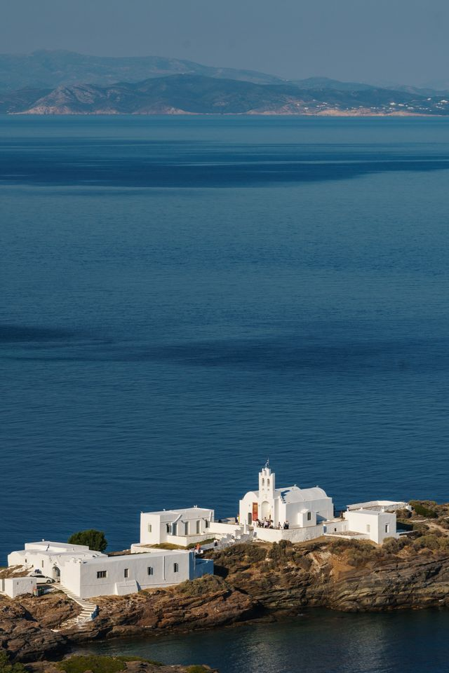 aerial shot of monastery of panagia chryssopigi est 1650, with dark blue sea and island of antiparos in the background, sifnos, cyclades islands, greece