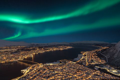 Aerial view at night from Storsteinen hill on Tromso city with beautiful shapes of aurora borealis