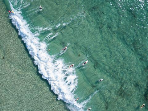 Aerial View of clean ocean waters with surfers