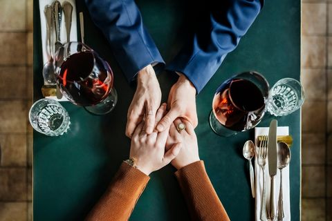 aerial view of couple holding hands at restaurant table