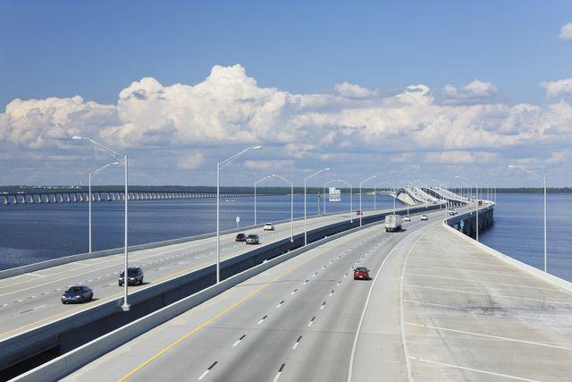aerial view of highway bridge across bay under blue sky