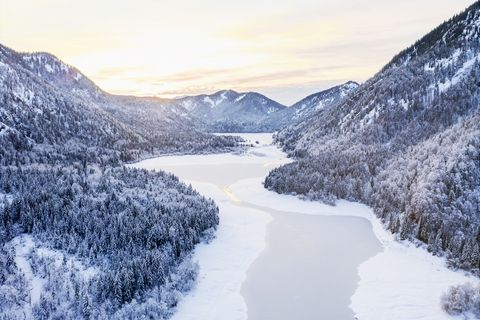 aerial view of snow covered landscape and frozen lake