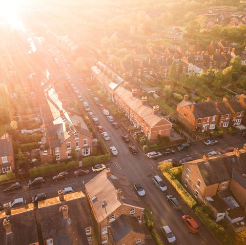 Aerial view of the sun setting over a cross roads in a traditional UK suburb