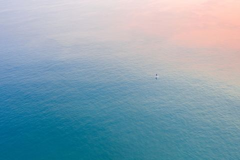 Aerial View of the sunrise colors reflecting on the blue ocean with a single surfer
