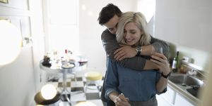 Affectionate young couple hugging, cooking in apartment kitchen