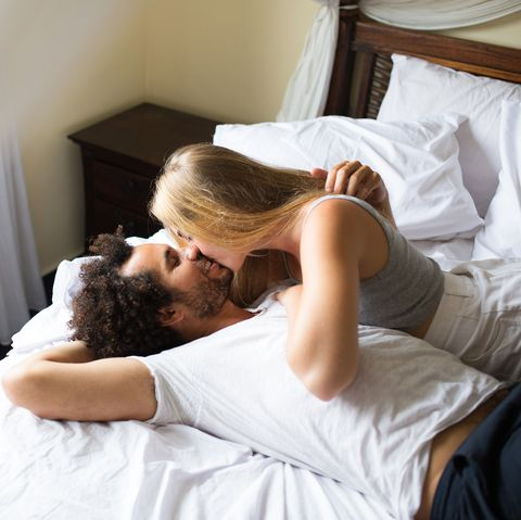 Affectionate young couple kissing in bed