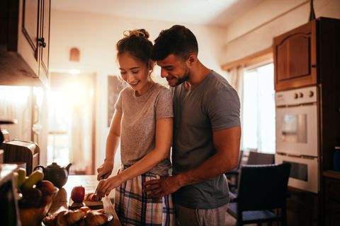 affectionate young couple preparing breakfast in the kitchen together
