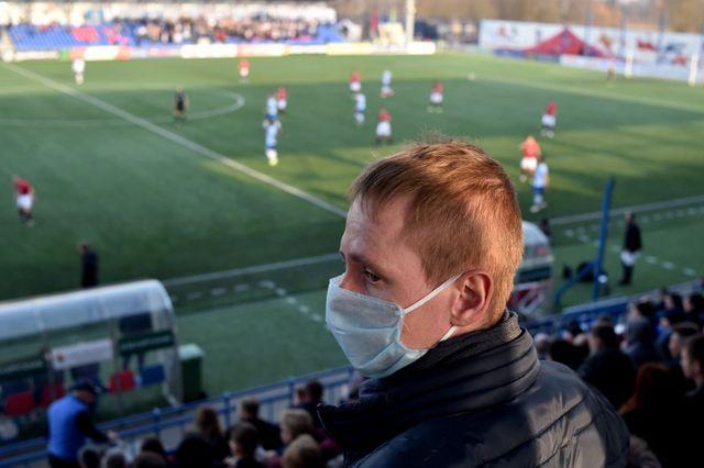 un aficionado ve un partido de fútbol con mascarilla en la grada
