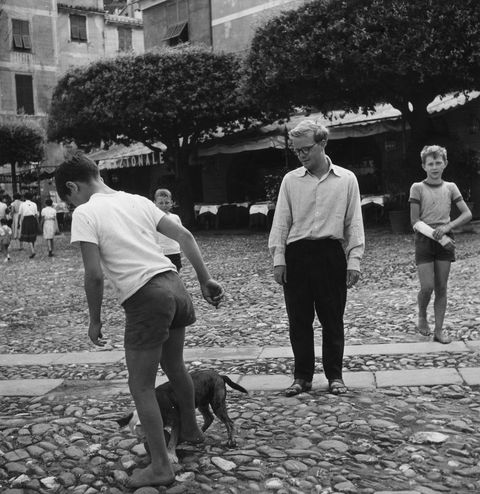 american writer truman capote watching a boy playing with his bulldog portofino, 1953