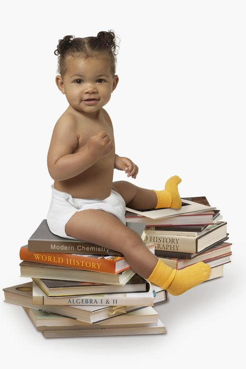 African American baby sitting on stack of books