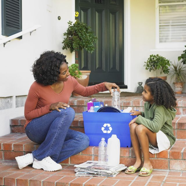 African American mother and daughter filling recycling bin
