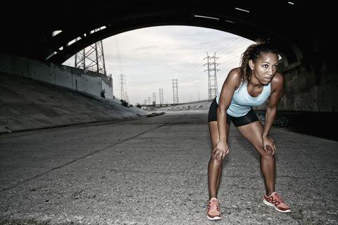 African American runner resting under overpass