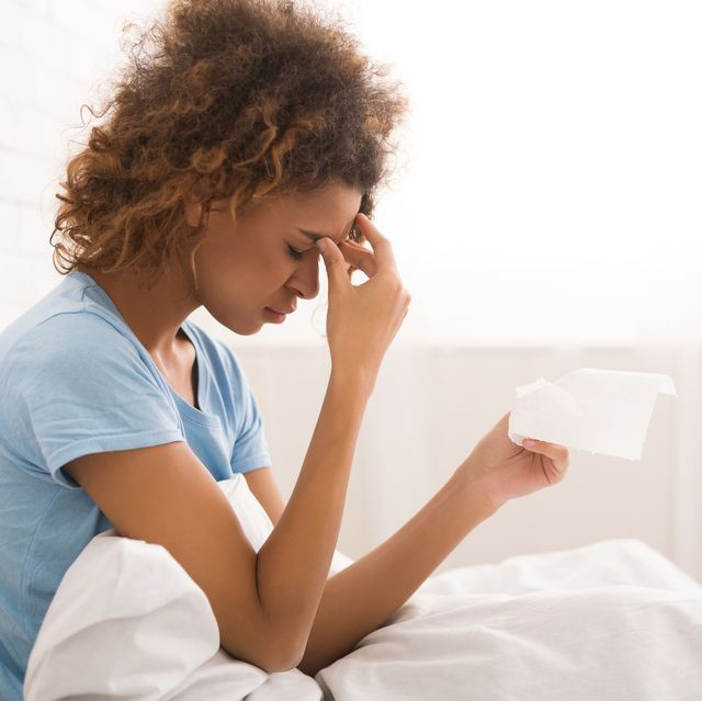 african american sick woman with runny nose, sitting in bed