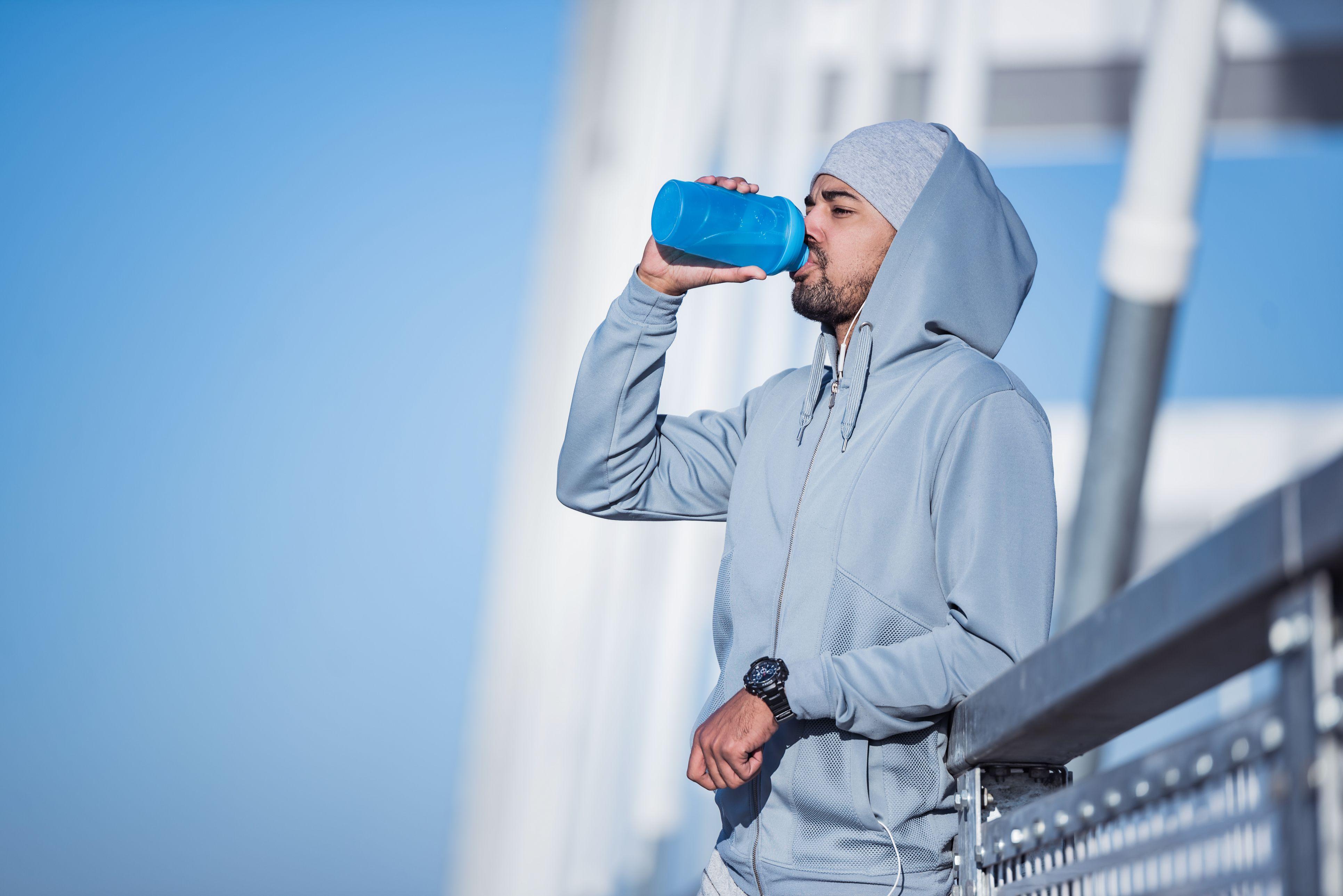 African American sportsman drinking water.