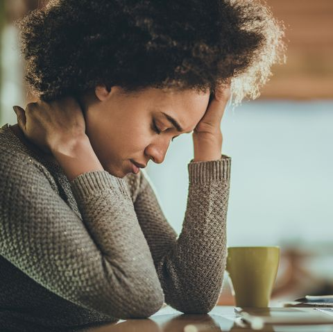 african american woman having a headache from working on a computer at home