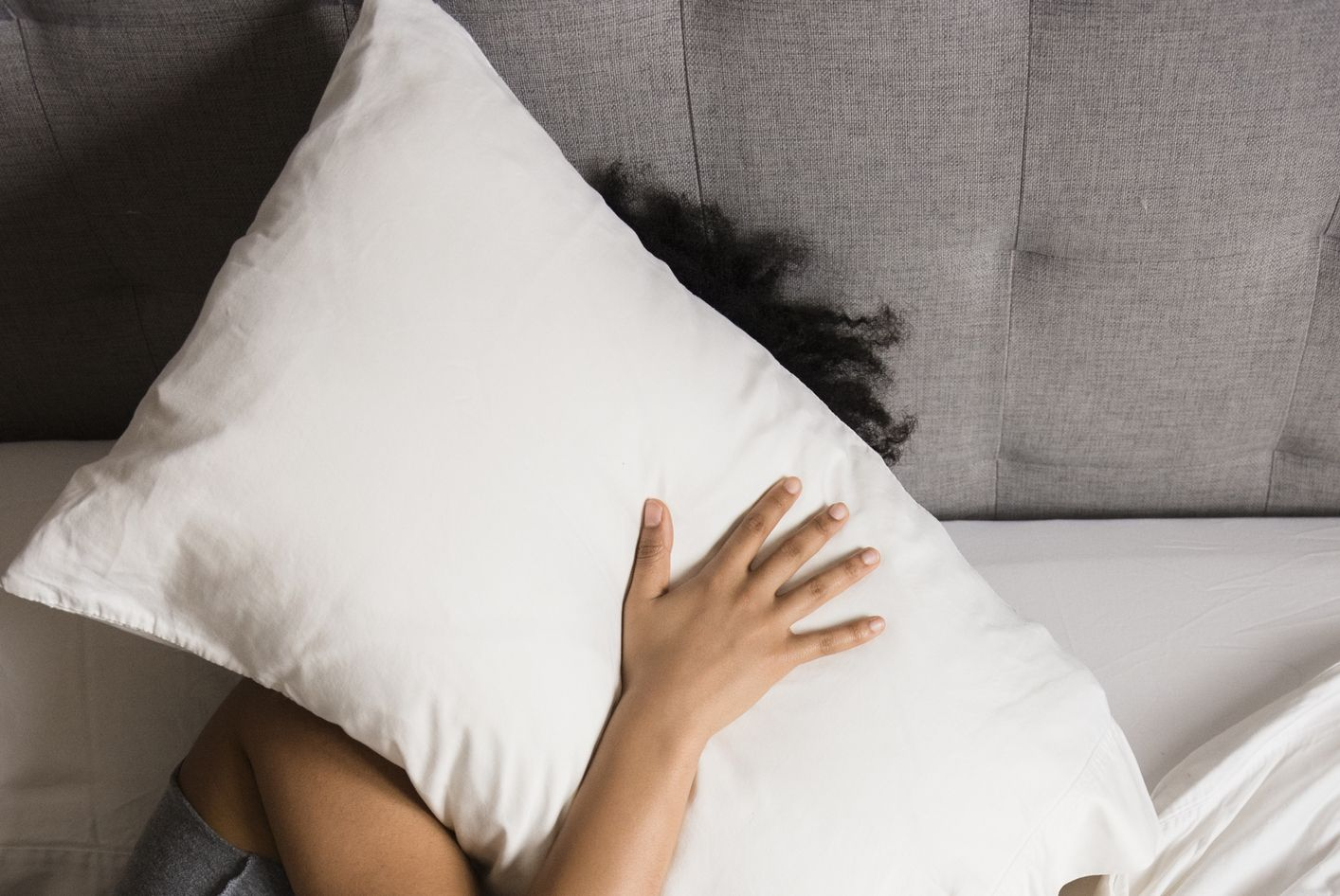 African American woman laying on bed hiding face under pillow