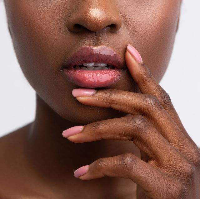 african american woman touching lips with shiny lip gloss