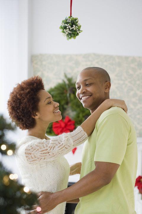black couple kissing underneath mistletoe