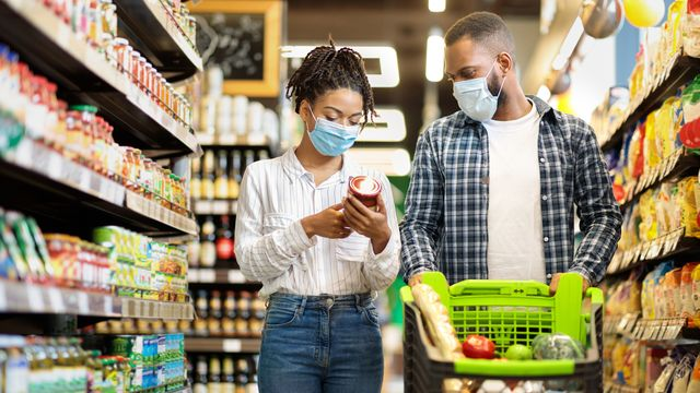 african family in shop buying groceries wearing face masks, panorama