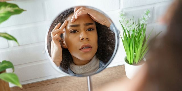 african teen girl feel worried about facial skin problem look in mirror young woman touch face squish pop zit pimple on forehead frustrated by blackheads black skin care problem, self care concept